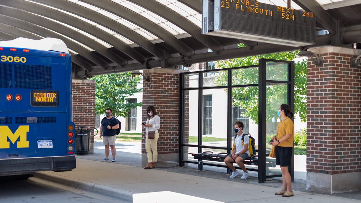 Students at a bus stop on Central Campus